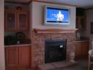 Half stone fireplace, wood mantel, and wall mount tv